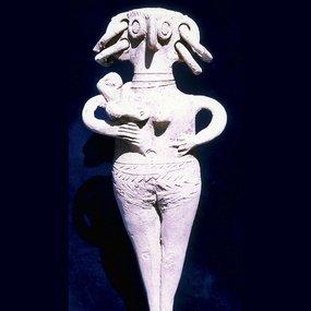 Ειδώλιο γυμνής γυναικείας μορφής με τρυπημένα αυτιά. Κρατά βρέφος. Ύ. 21 εκ. 15ος-13ος αι. π.Χ.. Κυπριακό Μουσείο.
